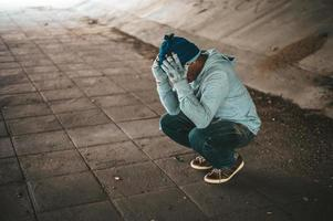 Homeless man sits under the bridge with both hands holding head
