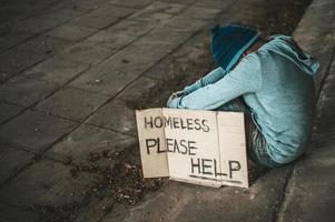 Beggar sits under bridge with a homeless message