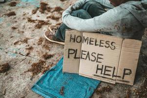 Beggar sleeps on the street with homeless messages please help photo