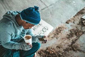 mendigo debajo del puente con una taza que contiene monedas y fideos instantáneos foto