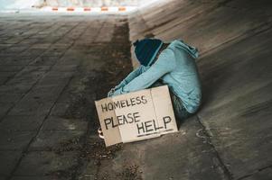 mendigo se sienta debajo del puente con un mensaje para personas sin hogar