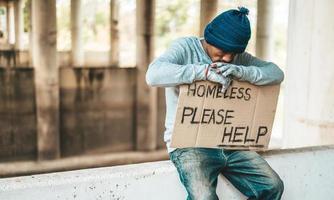 Mendigo se sienta en una barrera de la carretera con personas sin hogar, ayude a firmar foto