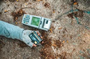 mendigo duerme en la calle con máquina de tarjeta de crédito foto