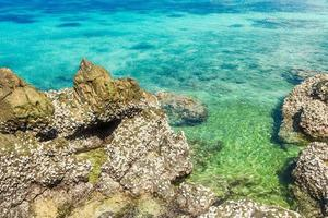 Tropical island rock with clear blue water