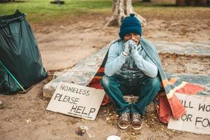 A beggar sitting outside with please help signs photo