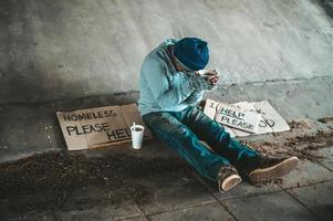 mendigo sentado debajo de un puente con una taza de dinero foto
