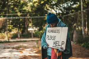 Beggar stands on the street with please help sign