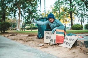 un hombre se sienta mendigando con personas sin hogar por favor mensaje de ayuda