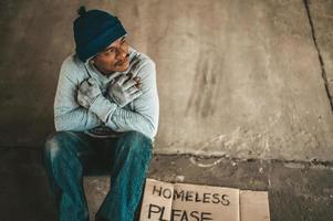 mendigo sentado debajo del paso elevado con una señal de ayuda por favor foto
