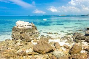 Tropical island rock on the beach with clear blue water and cloudy blue sky.