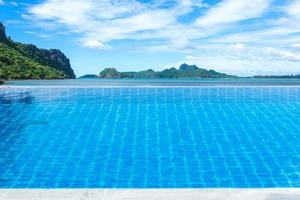 Swimming pool with ocean, mountains, and cloudy blue sky