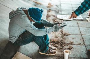 Beggars sitting under the bridge with a credit card swipe machine photo