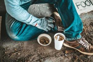 mendigo debajo del puente con una taza de fideos instantáneos y un cartel de ayuda foto