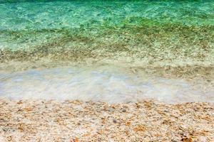 Olas del océano sobre guijarros en la playa