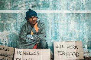 El hombre se sienta al lado de la calle con un mensaje para personas sin hogar.