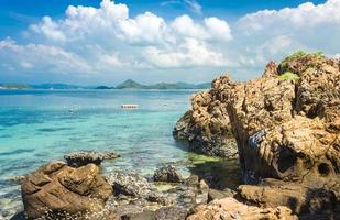 Rocas de la isla tropical en la playa por agua con nublado cielo azul foto