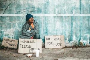 El hombre se sienta al lado de la calle con un mensaje para personas sin hogar. foto