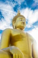 Golden Buddha statue with cloudy blue sky