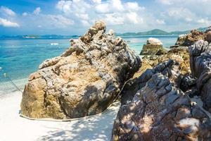 Roca de la isla tropical en la playa con cielo azul nublado foto