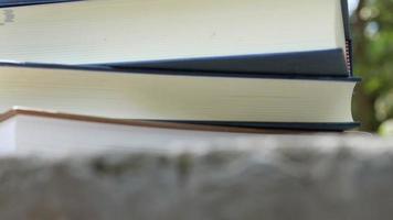pilha de livro grande com despertador vermelho no topo