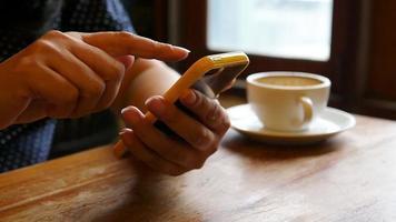 Señora con teléfono móvil en la cafetería con pastel