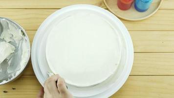 mulher decorando bolo de manteiga com creme video