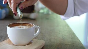 Primer plano de una dama vertiendo azúcar mientras se prepara una taza de café caliente.