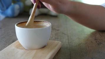 Primer plano de una dama preparando y comiendo una taza de café caliente