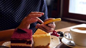 Señora con teléfono móvil en la cafetería.