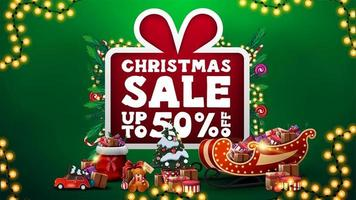 Christmas sale, up to 50 off, green discount banner with large cartoon present with large offer decorated with Christmas tree branches, candies, garlands and Christmas presents