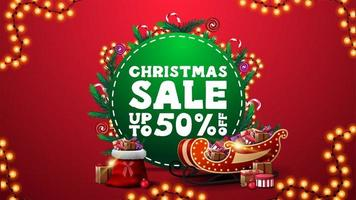 Christmas sale, up to 50 off, vertical red discount banner with green circle with offer, decorated with Christmas tree branches, candies and garlands and Santa Claus sleigh and bag with presents