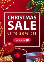 Christmas sale, up to 50 off, red vertical discount banner with presents, candy canes, Christmas tree branches and balloon on surface, top view