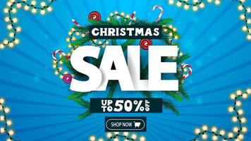 Christmas sale, up to 50 off, discount banner with volumetric text decorated of Christmas tree branches, candies and garlands.
