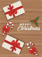 Feliz navidad letras con regalos y bastones en fondo de madera vector