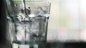 Closeup of soft drink bubbles in ice transparent glass video