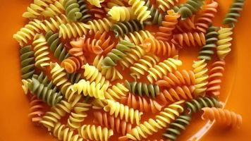 Raw Multicolored Macaroni Pasta Falling on a Plate video