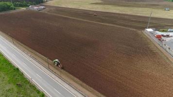 vista aerea di trattori che coltivano il campo per il grano invernale