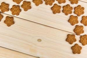 Snowflake-shaped gingerbread cookies on wood table photo