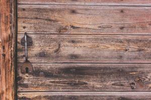 Metal door handle on a wood panel door photo