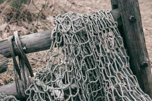 Detail of fishing net on wood bar