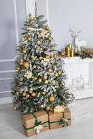 Christmas tree with decor and gifts in a white room photo