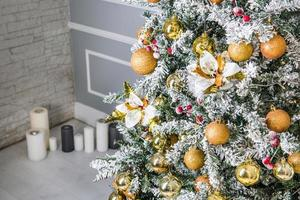 Decorated Christmas tree with golden ornaments and candles in background photo