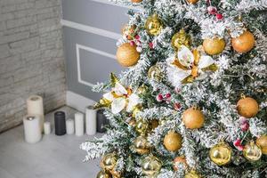 Árbol de Navidad decorado con adornos dorados y velas en segundo plano.