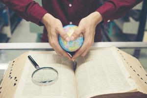 joven estudiante sosteniendo un modelo de tierra en la mano foto