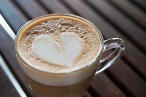 Close-up de taza de capuchino con patrón de leche en forma de corazón foto