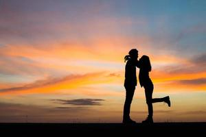 Silhouette of a couple together against beautiful sunset photo