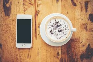 A cup of coffee and smartphone on wooden table in cafe