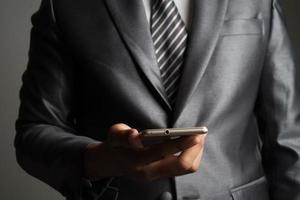 retrato, de, hombre de negocios, tenencia, smartphone, contra, fondo negro