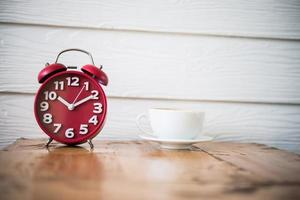 Red alarm clock with coffee on wooden table photo
