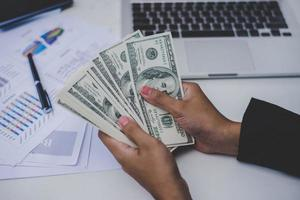 Business woman with dollars, close-up sitting at workplace